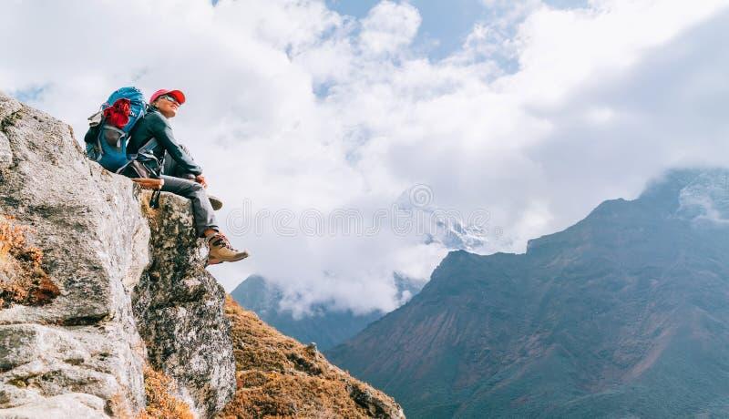 Jonge rugzaker-vrouwtje zit aan de rand van de afgrond en geniet van de Imja Khola-vallei tijdens het Everest Base Camp EBC op gr royalty-vrije stock fotografie