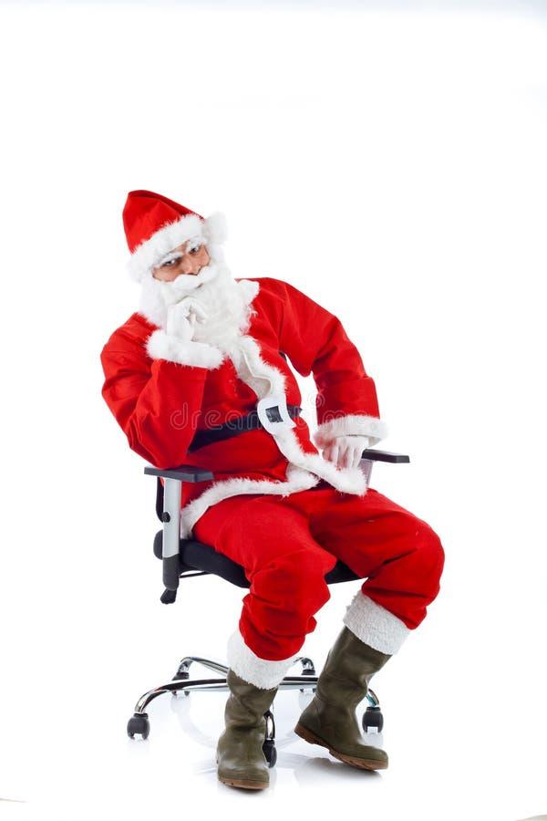 Jonge Santa Claus-zitting op een bureaustoel. stock fotografie