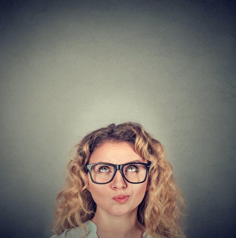 Jonge sceptische vrouw die omhoog kijken stock foto's