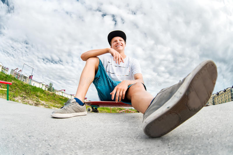 Jonge schaatser rustende zitting op zijn skateboard in een skatepark stock afbeeldingen