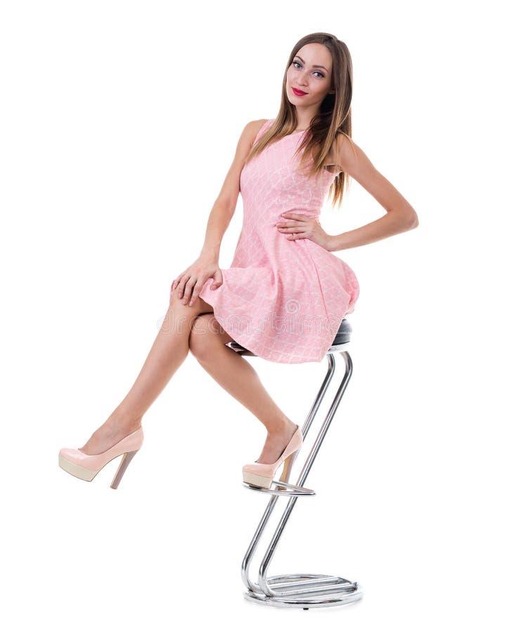 Jonge schitterende Kaukasische vrouw in roze kleding op de stoel stock foto's