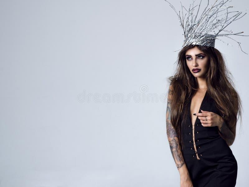 Jonge schitterende vrouw in een beeld van sexy houten heks stock afbeelding