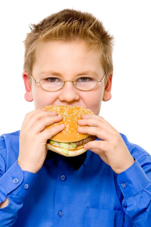 Jonge schooljongen die hamburger eet stock afbeelding