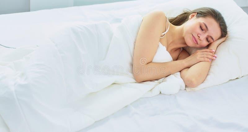 Jonge schoonheid in slaap in een wit bed royalty-vrije stock foto