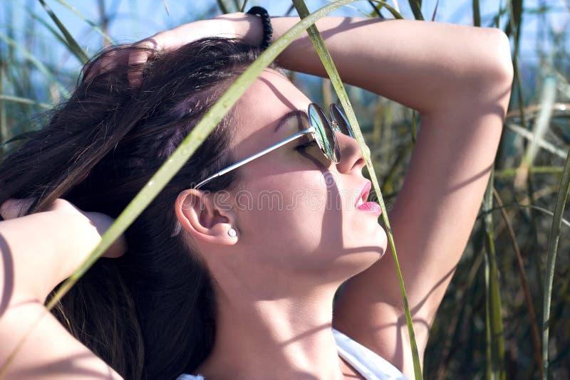 Jonge schoonheidsvrouw in aard die zonnebril dragen royalty-vrije stock fotografie