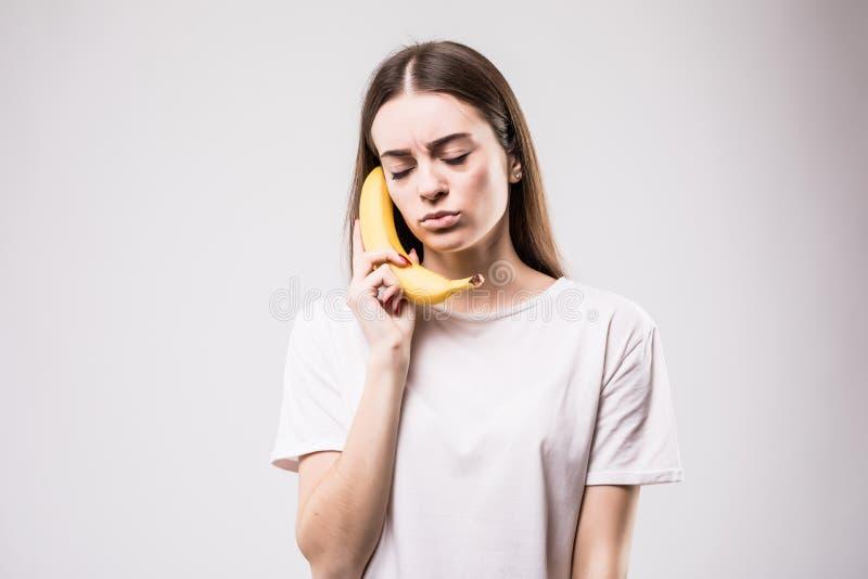 Jonge schoonheidsvrouw die met een banaan op een witte achtergrond roepen royalty-vrije stock foto's