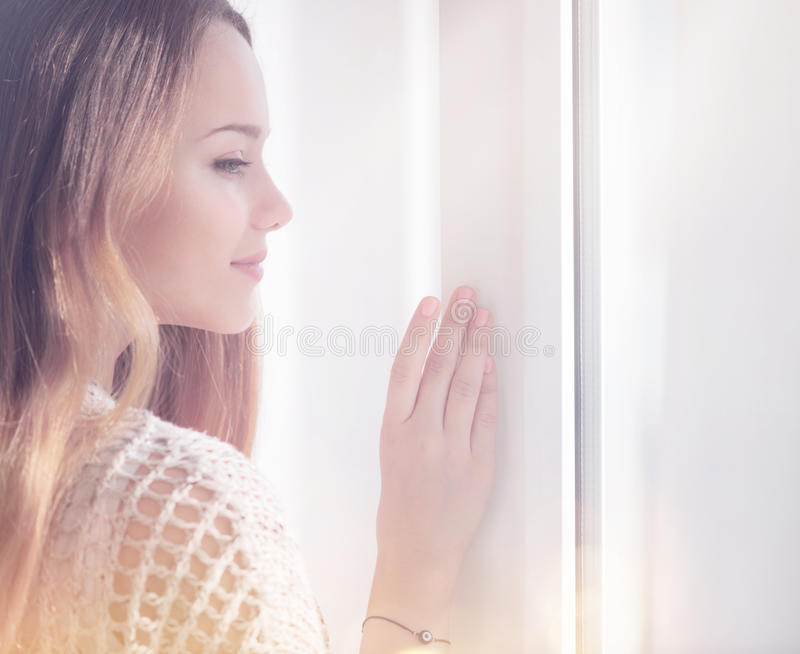 Jonge schoonheidsvrouw die uit het venster kijken stock afbeelding