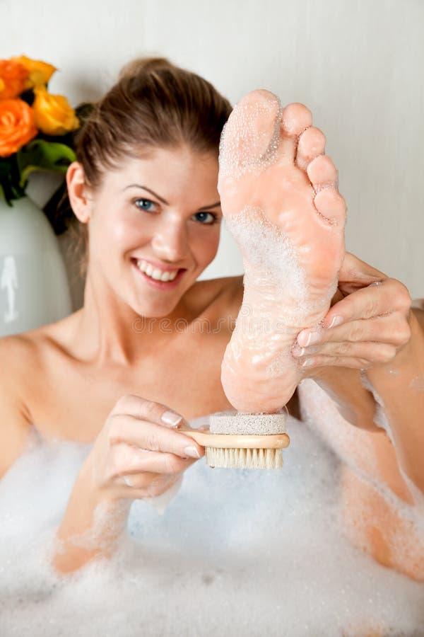 Jonge schoonheidsvrouw in het bad dat haar voet wast royalty-vrije stock fotografie