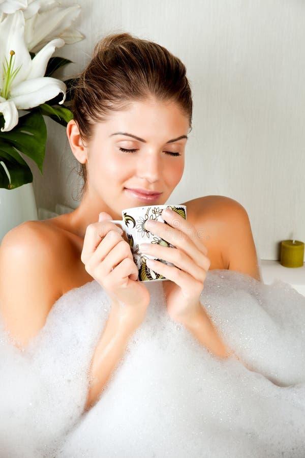 Jonge schoonheidsvrouw in het bad het drinken aftreksel royalty-vrije stock fotografie