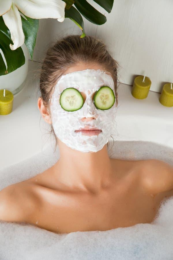 Jonge schoonheidsvrouw in het bad met gezichtsmasker royalty-vrije stock foto's