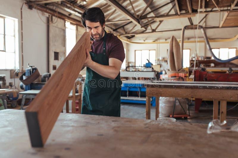 Jonge schrijnwerker die een plank van hout in zijn workshop onderzoeken royalty-vrije stock afbeeldingen