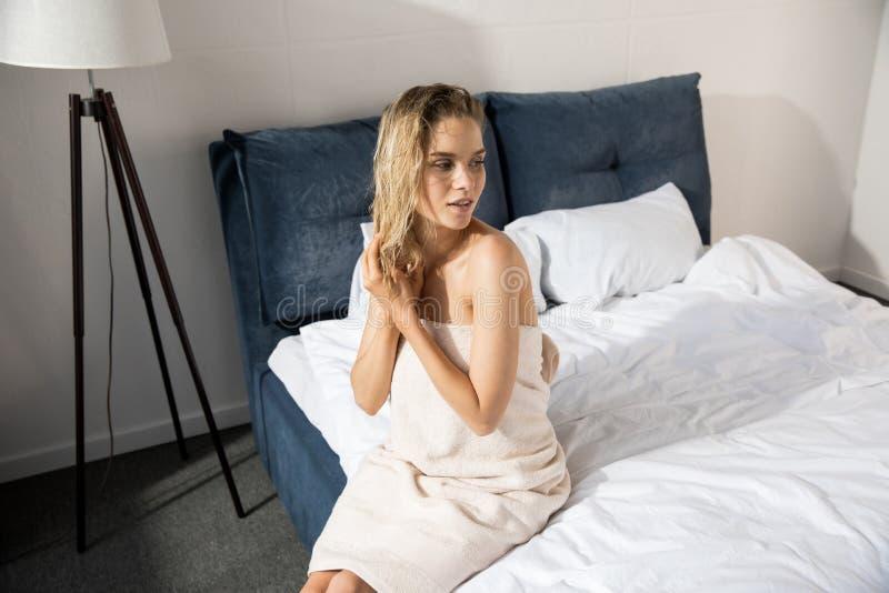 Jonge sensuele die vrouw omhoog met badhanddoekzitting wordt verpakt op bed royalty-vrije stock fotografie