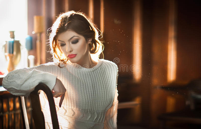 Jonge sensuele vrouwenzitting met venster op achtergrond Mooi meisje met wit comfortabel blousedagdromen binnen, alleen stock foto