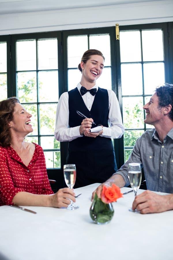 Jonge serveerster die terwijl het nemen van een orde van een paar lachen stock fotografie