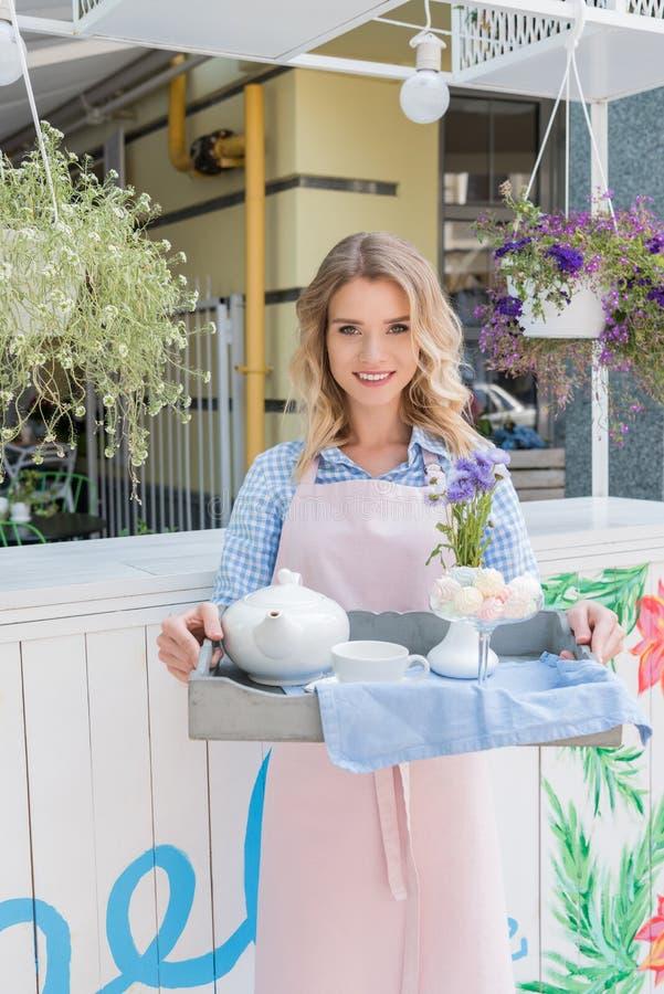 Jonge serveerster in het theestel van de schortholding op dienblad en het glimlachen bij camera in openluchtkoffie royalty-vrije stock afbeeldingen