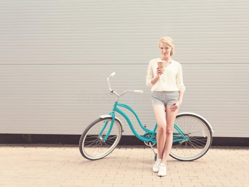 Jonge sexy blonde vrouw die zich dichtbij een groene uitstekende fiets bevinden en een kop van coffeehavepret en goede stemming h royalty-vrije stock foto