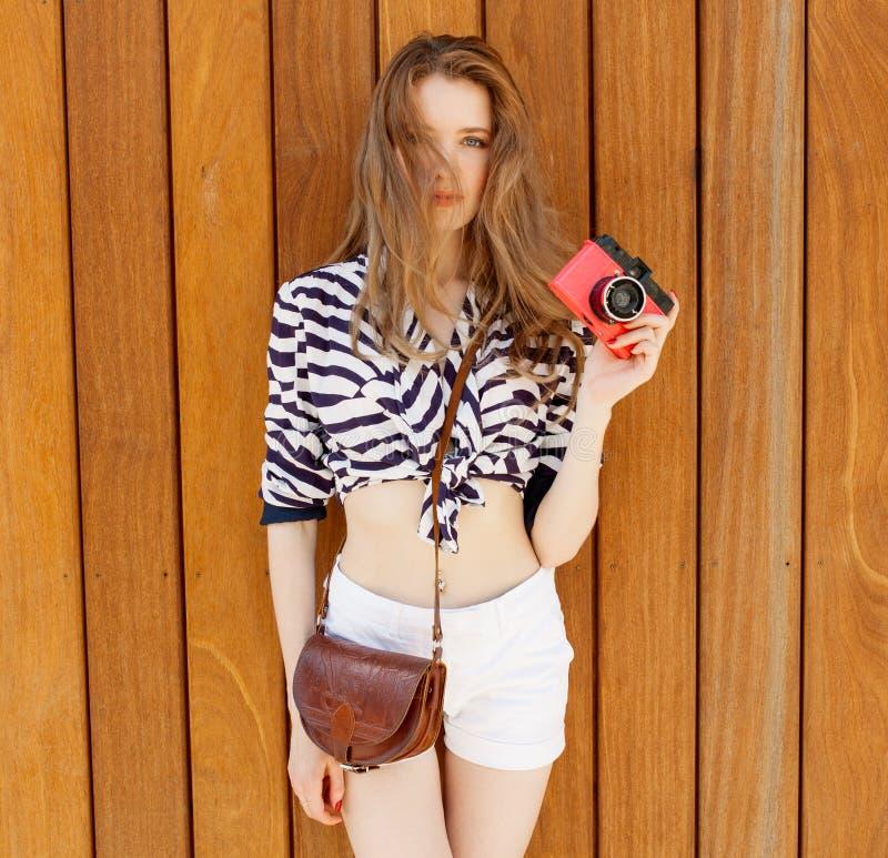 Jonge sexy glimlachende fotograaf vrouw, holding en het maken van beeld op retro uitstekende camera, die heldere mariene kleren,  stock fotografie