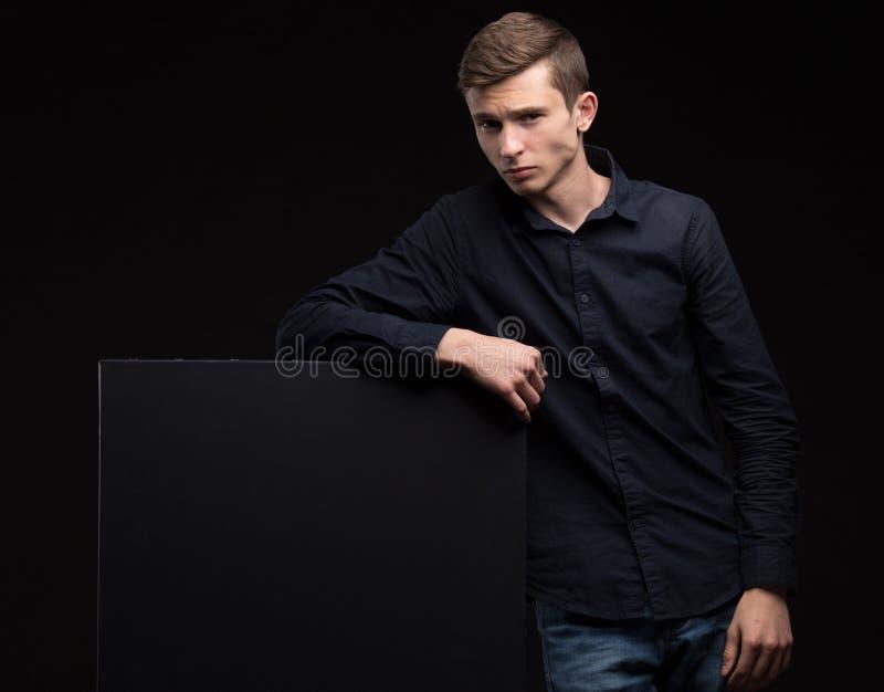 Jonge sexy mens die presentatie tonen, die op aanplakbiljet richten stock afbeeldingen