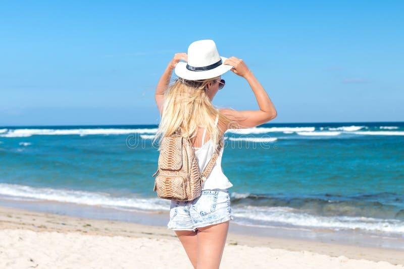 Jonge sexy vrouw die met witte hoed en luxe snakeskin pythonrugzak op wit zandstrand een tropisch eiland van Bali lopen royalty-vrije stock fotografie