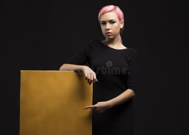 Jonge sexy vrouw die presentatie tonen, die op aanplakbiljet richten stock afbeelding