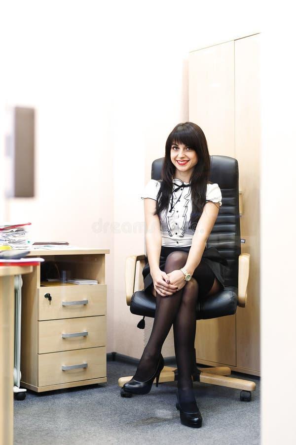 Jonge sexy vrouw die in zwarte kousen op werkplaats in offi zitten stock afbeeldingen