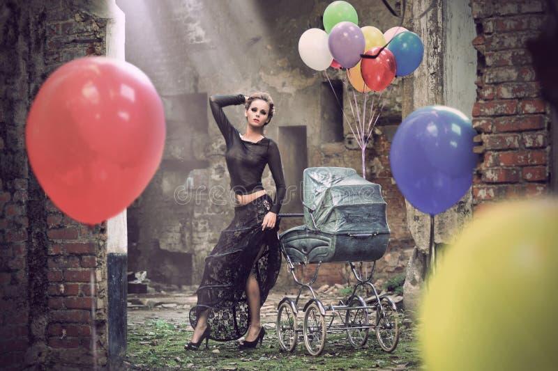 Jonge sexy vrouw met ballons en kinderwagen royalty-vrije stock foto