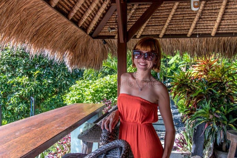 Jonge sexy vrouw in rode kleding in een tropische koffie op de achtergrond van palmen en tropische installaties Bali, Indonesië royalty-vrije stock fotografie