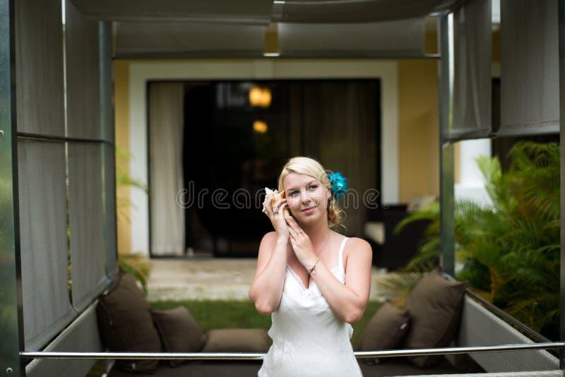 Jonge sexy vrouw in witte pegnoir met zeeschelp stock fotografie