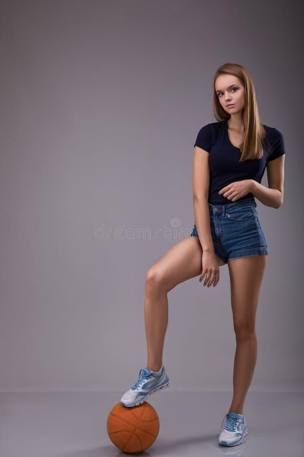 Jonge sexy vrouwelijke een gat makende in basketbalbal stock fotografie