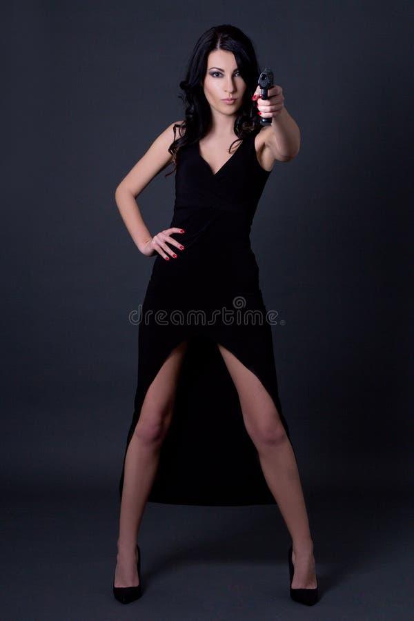 Jonge sexy vrouwengeheimagent in het zwarte kleding stellen met kanon ove stock afbeeldingen