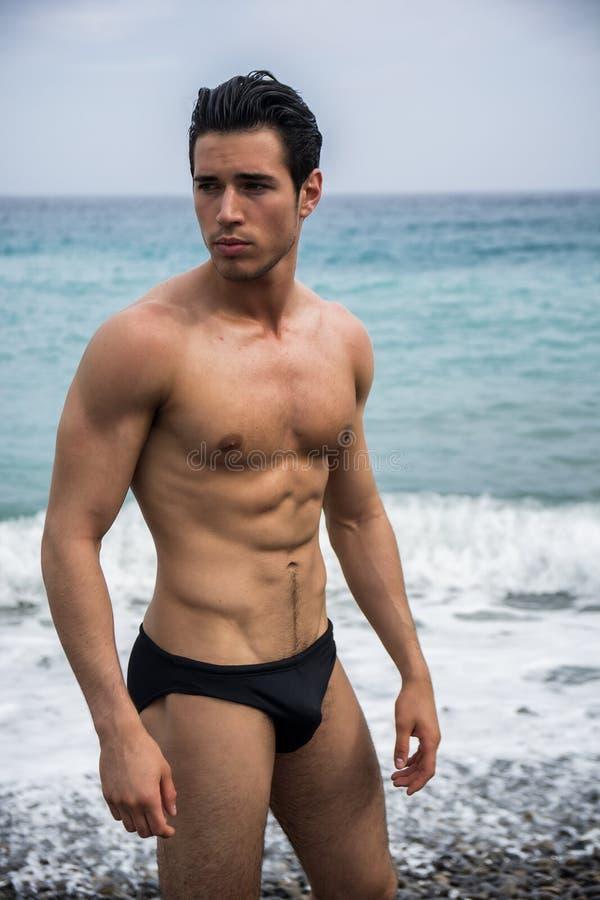 Jonge shirtless atletische mens die zich in water door oceaankust bevinden stock afbeelding
