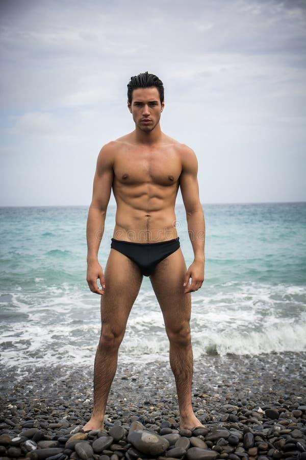 Jonge shirtless atletische mens die zich in water door oceaankust bevinden royalty-vrije stock fotografie