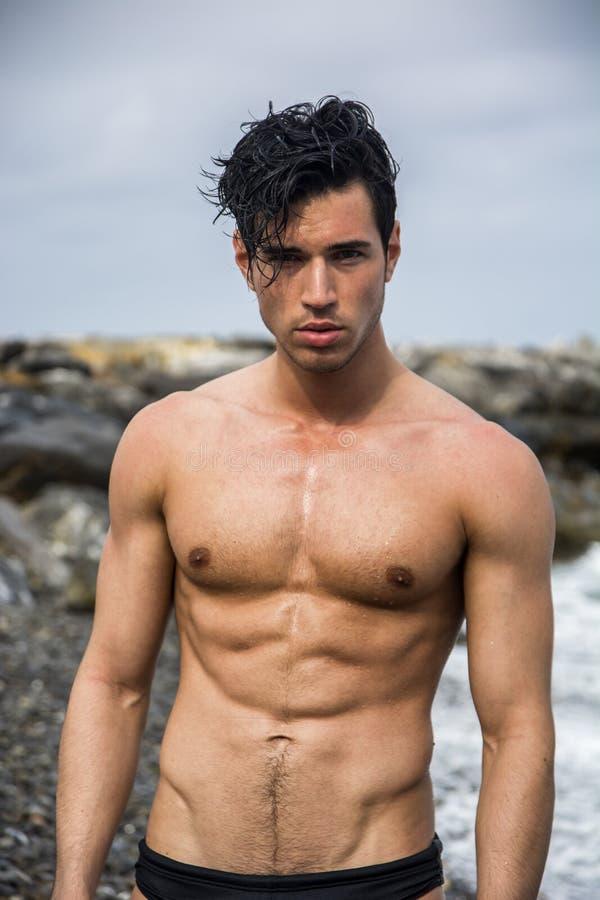 Jonge shirtless atletische mens die zich in water door oceaankust bevinden stock foto's