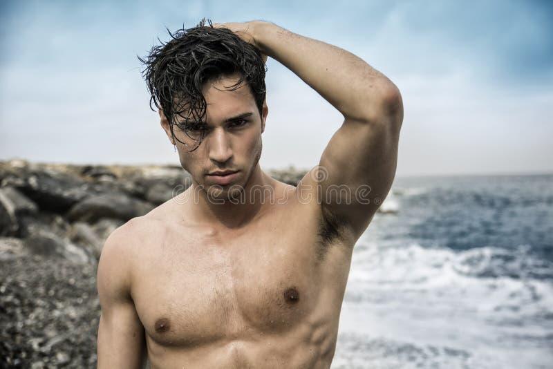Jonge shirtless atletische mens die zich in water door oceaankust bevinden royalty-vrije stock foto