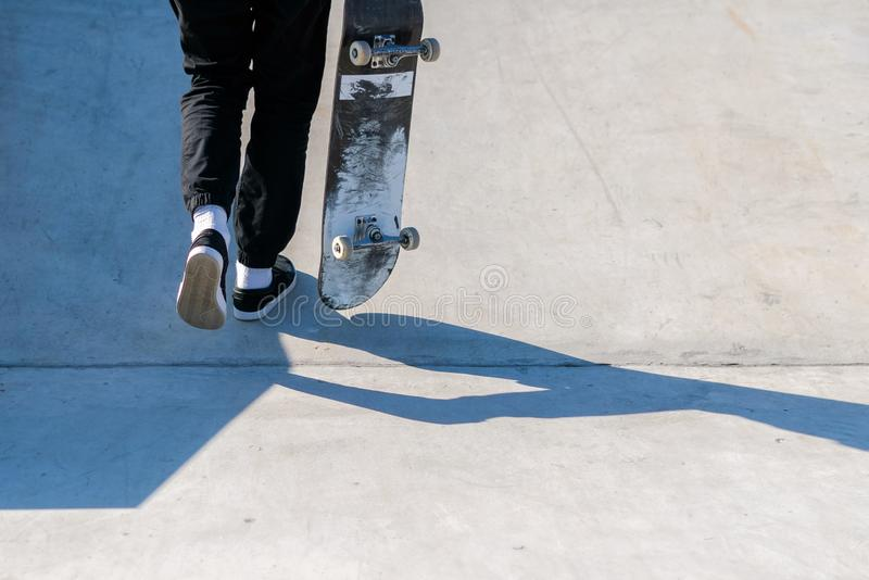 Jonge skateboardatleet die omhoog de helling lopen terwijl het houden van een skateboard Praktijkvrij slag, stedelijke extreme sp royalty-vrije stock foto's