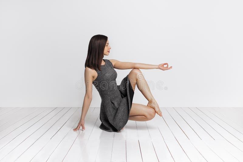Jonge slanke brunete vrouw in yogaklasse die mooie asanaoefeningen maken stock foto
