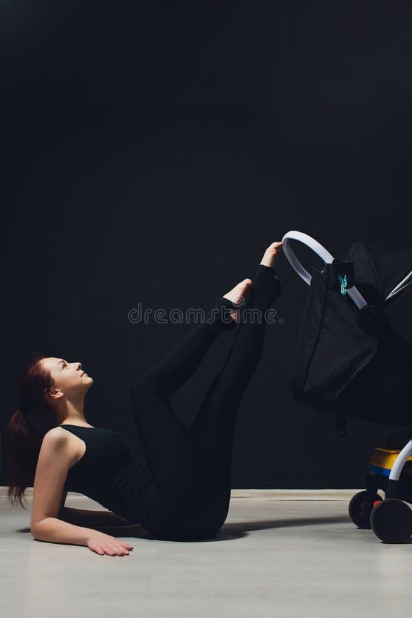 Jonge slanke moeder met een kinderwagen de jonge moeder heft haar been, acrobatiek, gymnastiek, sporten op royalty-vrije stock fotografie