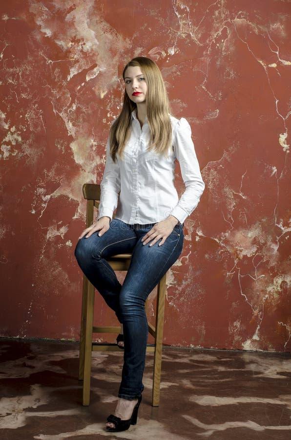 Jonge slanke mooie jonge blonde vrouw met lange benen en haar in Tumultoverhemd en jeans royalty-vrije stock foto's