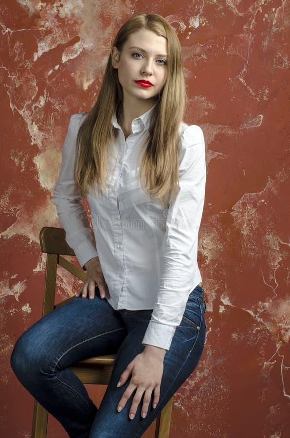 Jonge slanke mooie jonge blonde vrouw met lange benen en haar in Tumultoverhemd en jeans royalty-vrije stock afbeeldingen