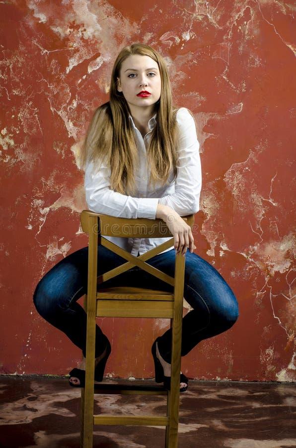 Jonge slanke mooie jonge blonde vrouw met lange benen en haar in Tumultoverhemd en jeans stock foto's