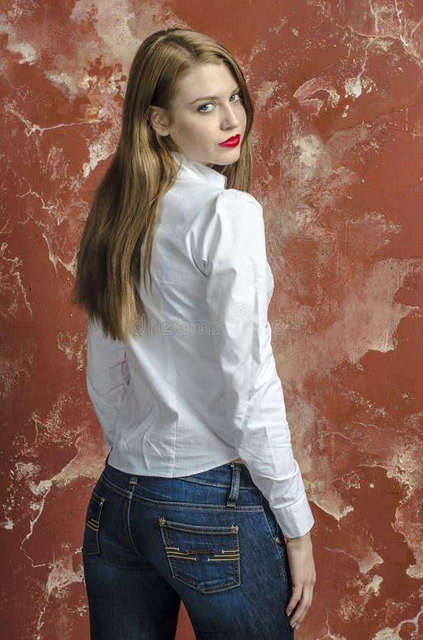 Jonge slanke mooie jonge blonde vrouw met lange benen en haar in Tumultoverhemd en jeans stock foto