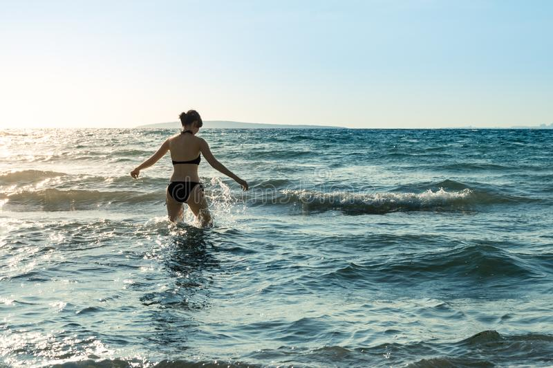 Jonge, slanke, sexy Kaukasische vrouwen zwarte bikinis die in het overzees met plonsen lopen stock afbeeldingen