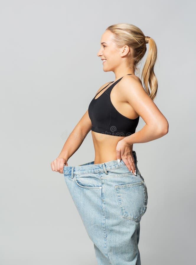 Jonge slanke sportieve vrouw in overmaatse broek stock foto's