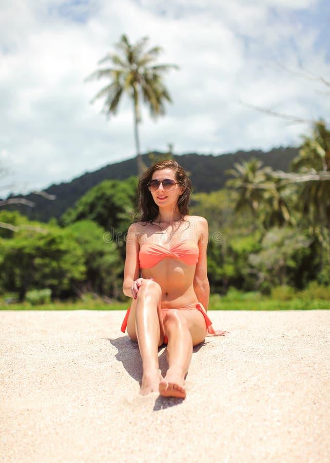 Jonge slanke vrouw in bikini en zonnebril die op fijn zandstrand zitten, wildernis met palmen achter haar royalty-vrije stock afbeelding