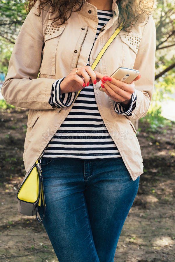 Jonge slanke vrouw die en een mobiele telefoon zich in openlucht bevinden met behulp van De lente stock afbeelding