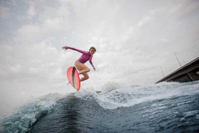 Jonge slanke vrouw die op de blauwe golf tegen de grijze hemel springen stock afbeeldingen
