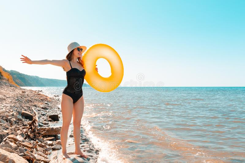 Jonge slanke vrouw met een bril en hoed houdt een oranje cirkel in haar handen zwemmen en geniet van de feestdagen Op de achtergr stock fotografie