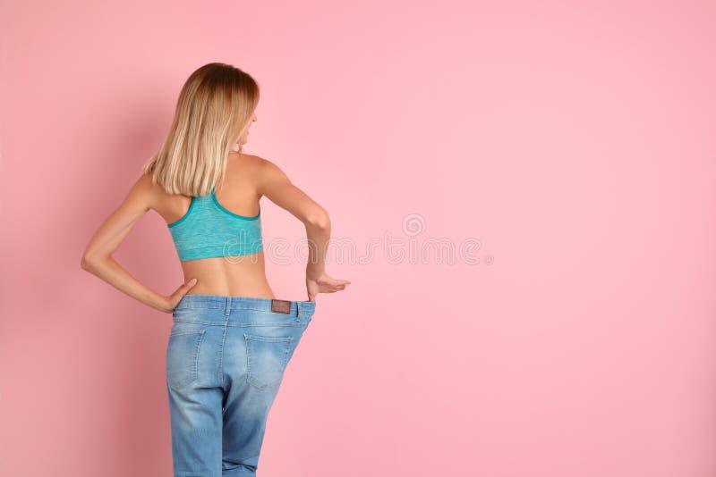 Jonge slanke vrouw in oude grote jeans die haar dieet tonen royalty-vrije stock afbeelding