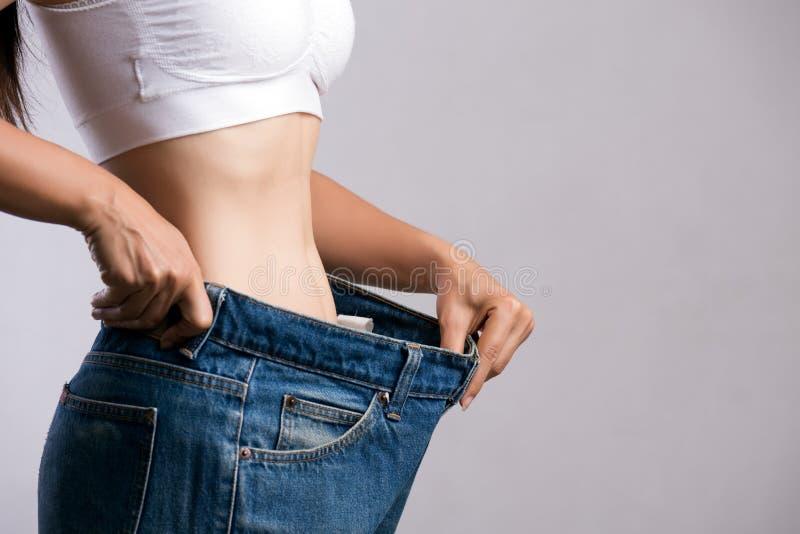 Jonge slanke vrouw in overmaatse jeans Geschikte vrouw die te grote broek dragen Gezondheidszorg en te verminderen de levensstijl stock afbeeldingen