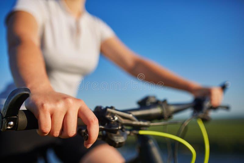 Jonge slanke vrouwenzitting op fiets, holdingssturen met handen Vrouw in de verlichting van de parkzonsondergang stock foto's